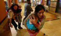 Women carrying children run for safety during the Westgate shopping mall attack in Nairobi, Kenya